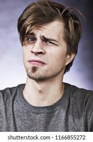 ライラックの背景に灰色のTシャツに斜視の若い男の不審な若い男のスタジオポートレート