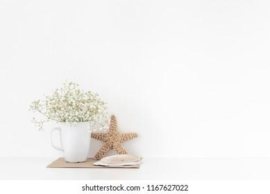 Achtergrond met stationair, schelpen, sea star, boeket van witte bloemen in mok op witte muur achtergrond, schattig zacht huisdecor. Kopieer ruimte voor tekst. Lege ruimte voor belettering. Goede koop zomer