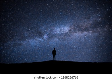 The man standing on the picturesque starry sky background