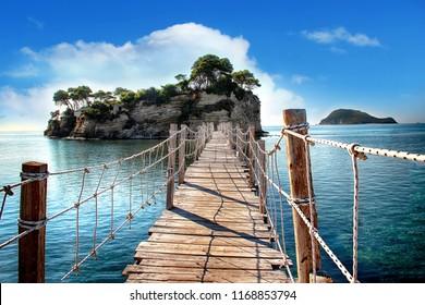 海を見下ろす木製の橋は、ヤシの木のある島へと続いています。ロープのつり橋です。ギリシャのザキントスにあります。