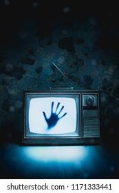 Imagen de alto contraste de un viejo televisor vintage con una mano dentro