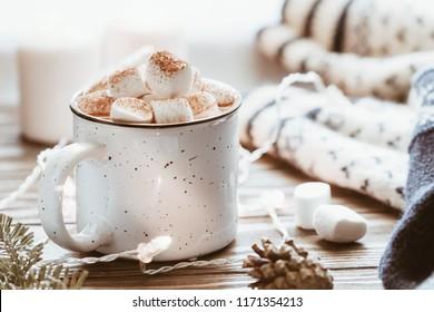 Chocolate caliente con malvaviscos en una taza de cerámica blanca rodeada de cosas de invierno en una mesa de madera. El concepto de vacaciones acogedoras y Año Nuevo.