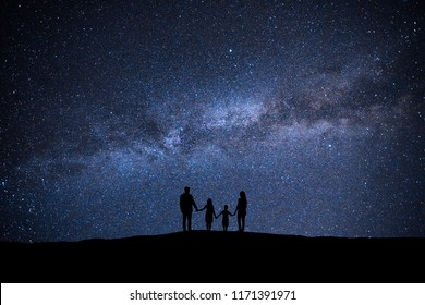 The family standing on the picturesque starry sky background