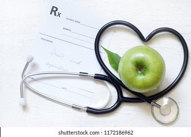 Gesundes Zeichenkonzept der alternativen Medizin mit Stethoskopherz und grünem Apfel auf weißem Hintergrund