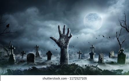 不気味な夜に墓地から立ち上がるゾンビの手