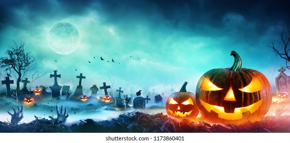 Jack O' Lanterns And Zombie Hands Rising Out Of A Graveyard In Misty Night