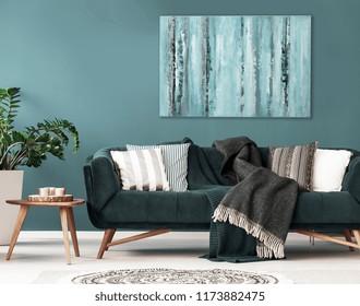 Cojines estampados en el sofá junto a la mesa de madera y la planta en el interior del apartamento oscuro. Foto real