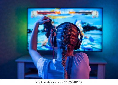 A gamer or a streamer girl at home in a dark room with a gamepad playing with friends on the networks in video games. A young man sits in front of a monitor or TV.