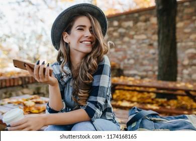 Bonita chica riendo con smartphone tiene un buen rato en el fin de semana de otoño. Retrato al aire libre de la adorable dama de moda con cabello castaño lleva sombrero en el día de octubre.