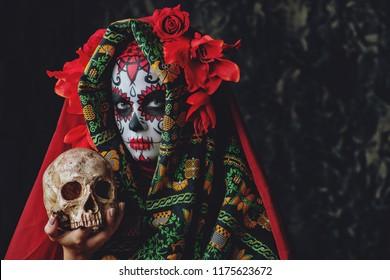 Calavera Catrina sosteniendo una calavera sobre un fondo oscuro y aterrador. Maquillaje de calavera de azúcar. Dia de los muertos. Dia de los Muertos. Víspera de Todos los Santos.