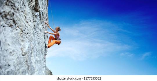 Seitenansicht der jungen schlanken Klettererin in leuchtend orangefarbenen Hosen, die auf der Klippe klettern. Eine Frau klettert auf eine vertikale Felswand auf dem Hintergrund des blauen Himmels