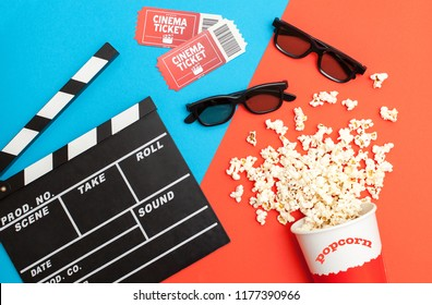 Movie time concept, Flat lay, Cinema background. Film watching.Top view of delicious popcorn, 3d glasses, movie tickets and movie clapper on a bright blue-red background
