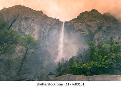Romantischer verschwommener Wassernebel des großen Yosemite Bridalveil Falles im Yosemite Valley National Park, Kalifornien, USA im Sommer. Pastellrosa orange weicher nebliger oder Feuerrauch bewölkter Himmelhintergrund.