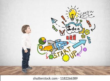 Vista lateral de un adorable niño caucásico con cabello rubio con camisa blanca y jeans azul oscuro y mirando hacia arriba. Colorido boceto de puesta en marcha en muro de hormigón