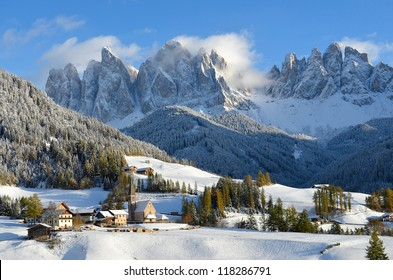 St. Magdalena or Santa Maddalena with its characteristic church in front of the Geisler or Odle dolomites mountain peaks in the Val di Funes (Villnosstal) in Italy in winter.