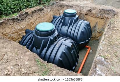 Zwei unterirdische Lagertanks aus Kunststoff, die zur Ernte eines Regenwassers unter der Erde aufgestellt wurden.