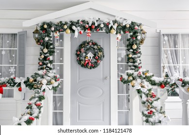 Christmas morning. porch a small house with a decorated door with a Christmas wreath. Winter fairy tale.