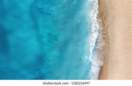 上面からのビーチと波。上面から見たターコイズブルーの水の背景。空気からの夏の海の景色。ドローンからの上面図。旅行のコンセプトとアイデア