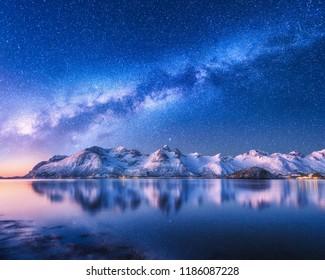 ノルウェーの冬の夜、雪に覆われた山と海の上の明るい天の川。雪に覆われた岩、星空、水の反射、フィヨルドのある風景。ロフォーテン諸島。スペース。美しい天の川
