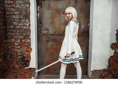 Chica anime con poses de espada en fábrica abandonada