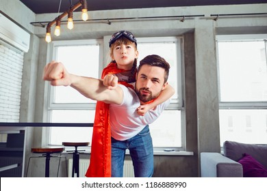 Vader en dochter kind in pakken superheld spelen in de kamer.