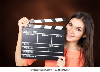 Young woman with movie clapper