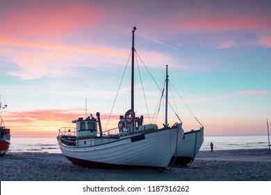 色鮮やかな夕焼けでデンマークのビーチに横たわるかわいい小さな漁船が、完璧なスカンジナビアの夏休みの思い出を作り出します。デンマーク、北海のスカゲラクにある北ユトランド半島のロッケン