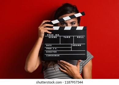 Frauenporträt, das Filmklöppel gegen bunten roten Hintergrund hält.