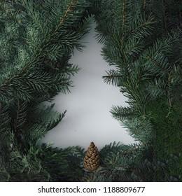 Negativer Raum-Weihnachtsbaumkonzept. Kreatives Winterlayout mit immergrünen Ästen. Flach liegen.