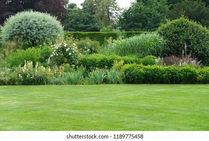 Vista panorámica de un hermoso jardín paisajista de estilo inglés con un césped verde cortado y un colorido macizo de flores