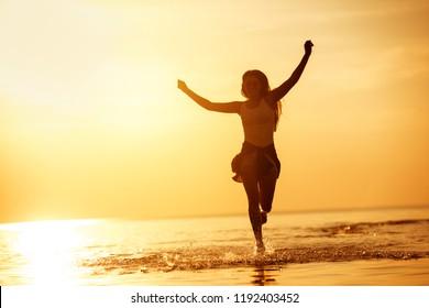 Gelukkig meisje loopt in kalm meerwater tegen zonsondergang