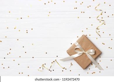 regalo y destellos de confeti en una vista superior de fondo de color. minimalismo, flatlay