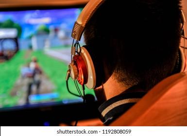 Ein junger Spielerjunge, der Videospiele am Computer spielt Kopfhörer und bunte Tastatur trägt