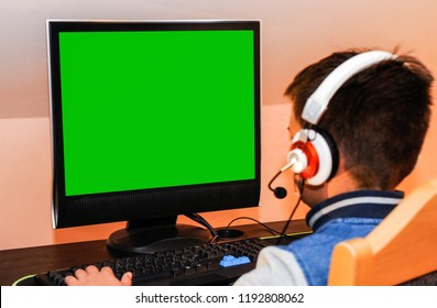 Een jonge gamerjongen die videospelletjes op computer speelt die hoofdtelefoons en kleurrijk toetsenbord draagt