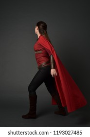 full length portrait of brunette girl wearing red medieval costume and cloak. standing pose  with back to the camera on grey studio background.