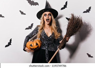 Surprised blonde girl screaming on white background with bats. Gorgeous young witch chilling at vampire party.