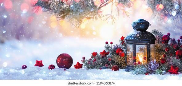 Weihnachtslaterne auf Schnee mit Tannenzweig im Sonnenlicht. Winterdekoration Hintergrund