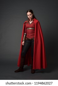 full length portrait of brunette girl wearing red medieval costume and cloak. standing pose   on grey studio background.
