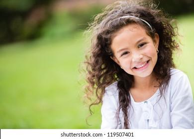 Dulce niña al aire libre con el pelo rizado en el viento