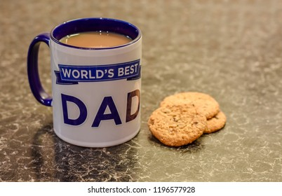 Worlds best Dad mug on the kitchen side with biscuits and tea bags