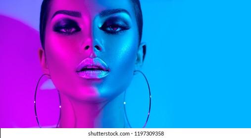 High Fashion Model Metallic Silber Lippen und Gesicht Frau in bunten hellen Neon UV blau und lila Lichter, posiert im Studio, schönes Mädchen, leuchtendes Make-up, bunte Make-up. Glitter Lebendiges Neon Make-up