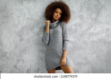 若い黒人女性はハイネックウールとカシミアの特大セーターを着ています