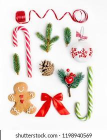 Composición de Navidad laicos plana con ramas de abeto, galleta de Navidad de jengibre y adornos navideños sobre fondo blanco. Vista superior.