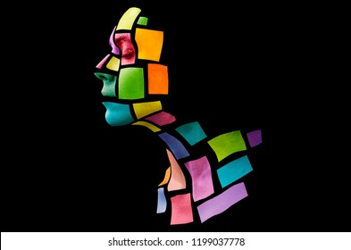 Portrait of a young woman with bold glowing makeup posing in the studio. Shape of colored squares on female face. Isolated on black background.