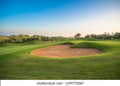 Búnker de arena en forma de corazón en el campo de golf verde.