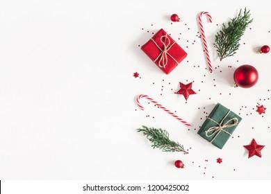 Weihnachtskomposition. Geschenke, Tannenzweige, rote Verzierungen auf weißem Hintergrund. Weihnachts-, Winter-, Neujahrskonzept. Flache Lage, Draufsicht, Kopierraum