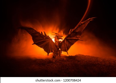 Silueta de dragón que escupe fuego con alas grandes sobre un fondo oscuro de fuego ardiente. Enfoque selectivo