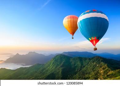 Coloridos globos aerostáticos volando sobre la montaña