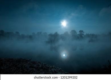 Paisaje místico de la noche. Luna llena sobre río brumoso.