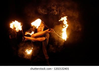 Feuershow. Feuertänzer jongliert mit zwei Stäben. Nachtvorstellung. Dramatisches Porträt. Feuer und Rauch.